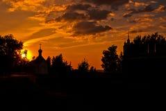Deux églises entre les arbres silhouettés pendant le coucher du soleil Image stock