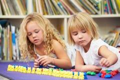 Deux élèves élémentaires comptant ensemble dans la salle de classe Photos stock