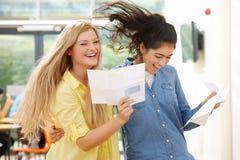 Deux élèves adolescents célébrant le résultat réussi d'examen photographie stock