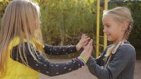 Deux élèves du cours préparatoire de petites filles dupant autour et jouant le petit-gâteau banque de vidéos