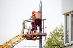 Deux électriciens travaillant avec le torse nu Image stock