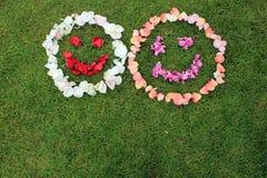 Deux émoticônes souriantes de visages des pétales de se sont levées sur le fond de Photographie stock