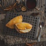 Deux épices dispersées par petits pains des clous de girofle de citron de cannelle Repassez la tasse de thé sur un fond foncé en  Image libre de droits