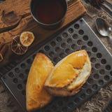 Deux épices dispersées par petits pains des clous de girofle de citron de cannelle Repassez la tasse de thé sur un fond foncé en  Photos libres de droits