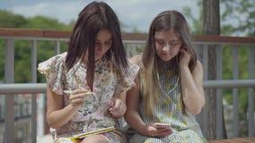 Deux étudiantes attirantes s'asseyant dehors ensemble Une fille écoutant la musique avec ses écouteurs, second banque de vidéos