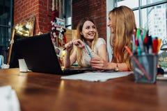 Deux étudiantes ayant une conversation amicale discutant se reposer devant l'ordinateur portable Photos stock