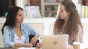Deux étudiantes diverses parlant l'étude ensemble dans le campus clips vidéos