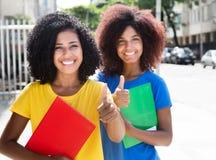 Deux étudiantes latines montrant le pouce Image libre de droits
