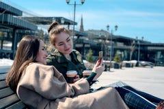 Deux étudiantes s'asseyent sur un banc en parc de ville et regardent le smartphone génération des instruments Photo stock