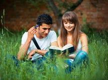 Deux étudiants étudiant en parc sur l'herbe avec le livre dehors Image stock