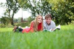 Deux étudiants affichant le livre sur une herbe Image libre de droits