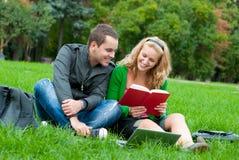 Deux étudiants affichant un livre sur l'herbe Image libre de droits