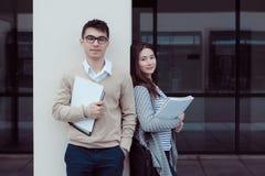 Deux étudiants attirants parlant et regardant dans le dossier à l'extérieur du bâtiment le campus Photographie stock