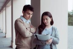 Deux étudiants attirants parlant et regardant dans le dossier le campus Photos libres de droits
