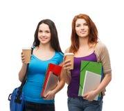 Deux étudiants avec le sac, les dossiers, le comprimé et le café Images stock