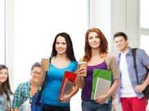Deux étudiants avec le sac, les dossiers, le comprimé et le café Photo stock