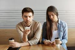 Deux étudiants beaux ont fatigué après étude, se reposant dans le cafétéria, buvant du café dans le silence, regardant par le soc Image stock