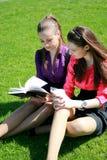Deux étudiants détendant sur l'herbe Image stock