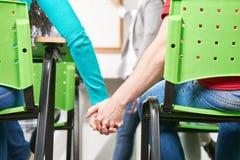 Deux étudiants dans des mains de prise d'amour Image libre de droits