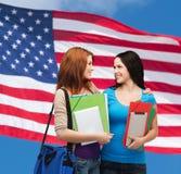 Deux étudiants de sourire avec le sac et les dossiers Image libre de droits
