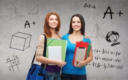 Deux étudiants de sourire avec le sac, les dossiers et le comprimé Image stock
