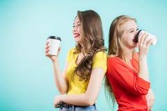 Deux étudiants de sourire ayant une tasse de café rire heureux de jeunes femmes, de nouveau au dos photo libre de droits