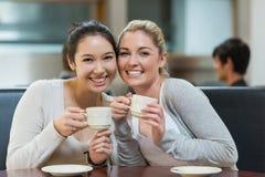 Deux étudiants de sourire dans le café d'université Images stock