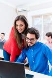 Deux étudiants discutant leur travail dans l'université Image stock