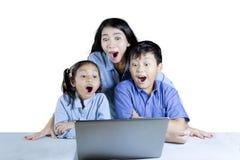 Deux étudiants et professeur choqués avec un ordinateur portable Photo stock