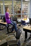 Deux étudiants féminins étudiant dans la bibliothèque Photos stock
