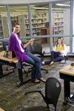 Deux étudiants féminins étudiant dans la bibliothèque Photographie stock libre de droits