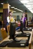 Deux étudiants féminins se tenant prêt des ordinateurs de bibliothèque Image libre de droits