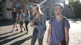 Deux étudiants heureux marchant sur le campus universitaire clips vidéos
