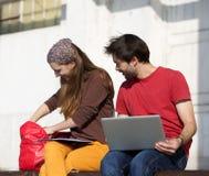 Deux étudiants heureux s'asseyant dehors avec l'ordinateur de dessus de recouvrement Photo stock