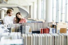 Deux étudiants lisant et étudiant dans la bibliothèque Photo libre de droits