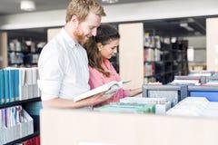 Deux étudiants lisant et étudiant dans la bibliothèque Image libre de droits