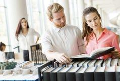 Deux étudiants lisant et étudiant dans la bibliothèque Photos stock