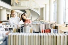 Deux étudiants lisant et étudiant dans la bibliothèque Images stock
