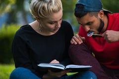 Deux étudiants lisant un livre, appréciant l'heure d'été Photos stock