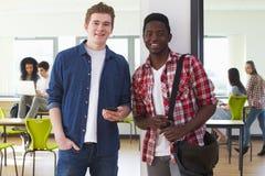 Deux étudiants masculins regardant le téléphone portable dans la salle de classe Photos stock