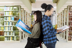 Deux étudiants multi-ethniques se tenant dans la bibliothèque Photo libre de droits
