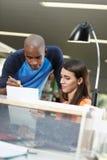 Deux étudiants observant l'essai dans la bibliothèque Image stock