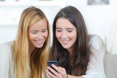Deux étudiants observant le contenu de media dans le téléphone intelligent Photographie stock libre de droits