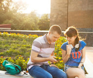 Deux étudiants ou adolescents avec le téléphone portable dehors Photo libre de droits