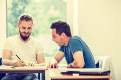 Deux étudiants parlant dans la salle de classe Photographie stock libre de droits