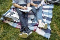 Deux étudiants se préparent au séminaire se reposant sur l'herbe Éducation en ligne Photographie stock libre de droits