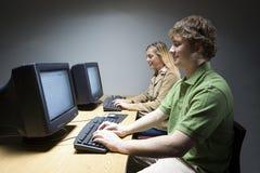 Deux étudiants travaillant sur des ordinateurs images stock