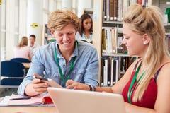 Deux étudiants universitaires étudiant dans la bibliothèque ensemble Photographie stock libre de droits