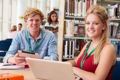 Deux étudiants universitaires étudiant dans la bibliothèque ensemble Photos stock