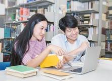 Deux étudiants universitaires asiatiques à l'aide de l'ordinateur portable dans la bibliothèque Photographie stock libre de droits